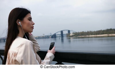 Young brunette woman in white jacket listening to the music with smart phone on the modern bridge. Morning exercise in megacity