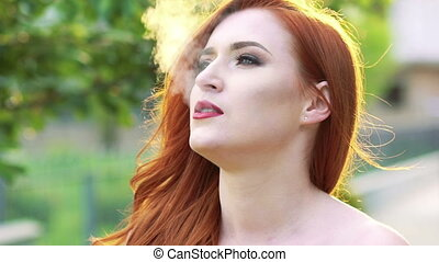 Close up woman face, exhales smoke outdoor Slow motion