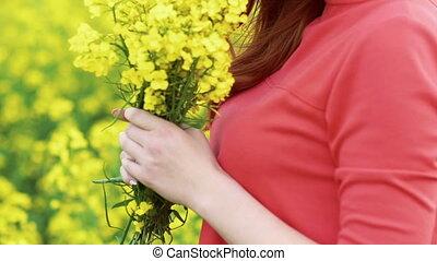 Close up girl face's profile smelling rape flowers bouquet. Slow motion