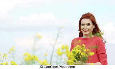 Girl with golden hair with bouquet of rape bloom smiling in the field. Slowly