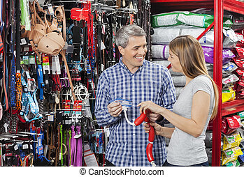 Happy Couple Buying Sausage Toy In Pet Store - Happy couple...