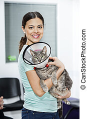 Mid Adult Woman Carrying Cat With Cone In Clinic - Portrait...