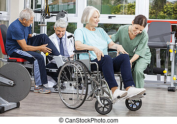 Senior People Being Assisted By Physiotherapists In Rehab...