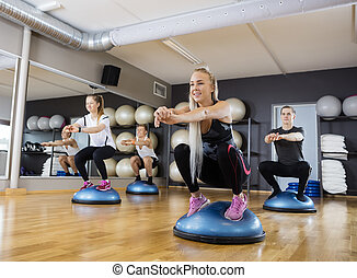 Friends Doing Squatting Exercise On Bosu Ball In Gymnasium -...