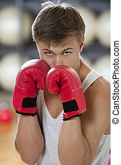 Confident Young Man Boxing In Gym - Portrait of confident...