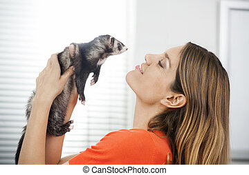 Loving Mid Adult Woman Playing With Weasel - Side view of...