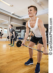 Man In Sportswear Lifting Barbell In Gym - Smiling young man...