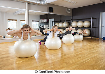 Friends Performing Back Extension Exercise On Balls - Young...
