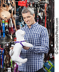 Customer Holding Dog Soft Toy At Pet Store - Happy mature...