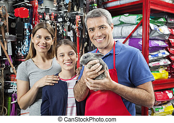 Happy Salesman Holding Rabbit While Standing With Family -...
