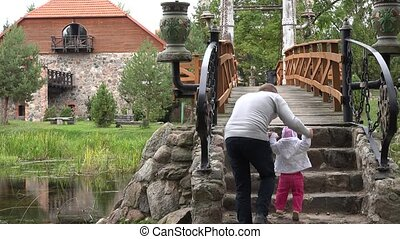 Man teach baby to walk on stone stairs and wooden bridge over river. 4K