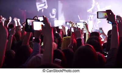 Making party at a rock concert and hold cameras with digital displays