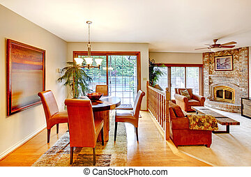 House with open floor plan. View of dining area with table set and brick fireplace in the living room.