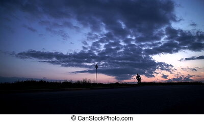 Silhouette of a man running on the road at sunset.