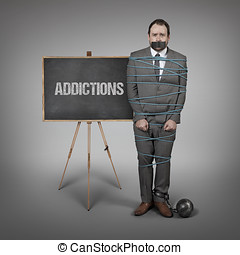 Addictions on blackboard with businessman tied with rope at...