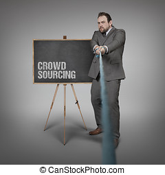 Crowd Sourcing text on blackboard with businessman pulling...