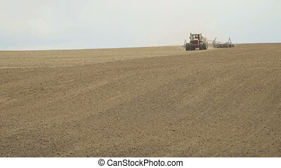 A tractor sows plowed field using a seeder. Season of sowing...