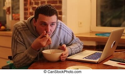 A man reaps hot food evening in front of a laptop - A man...