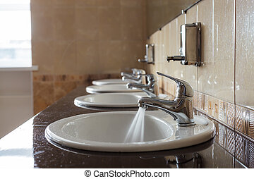 Water flows from the tap in a public toilet.