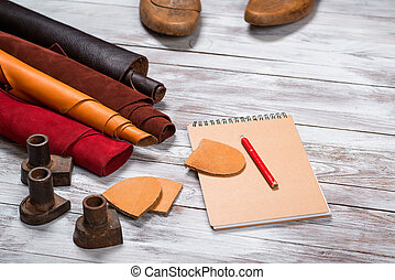 Brightly colored leather in rolls, working tools, shoe...