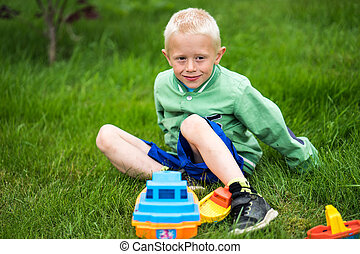 Little boy playing with his toys in the garden