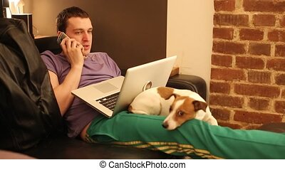 The man on the couch with a laptop and a dog