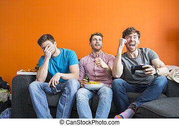 Men Palying Video Games - Group of three are having fun at...