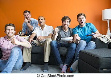 Guys playing video games - Group of men are having fun at...