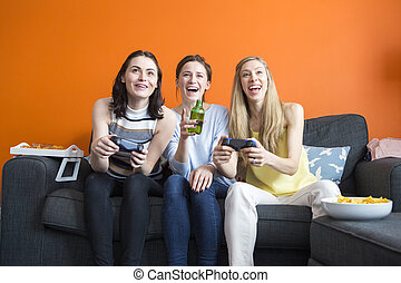 Girls playing video games - A group of girls are sat on the...