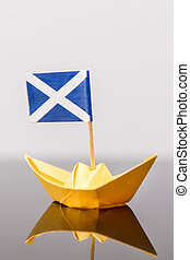paper ship with scots flag, concept independence and travel