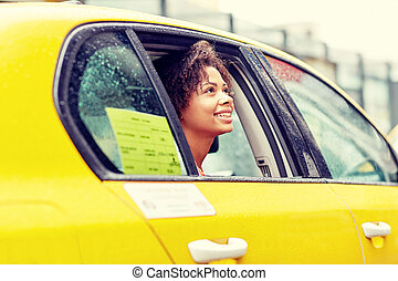 happy african american woman driving in taxi - business...