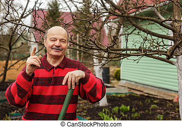 elderly man with a garden tool gives tips and tricks for...