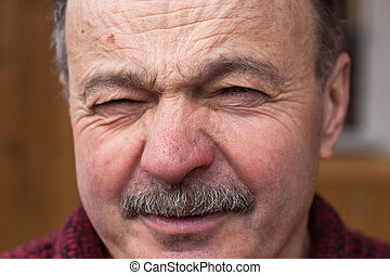 Elderly man with disdain looking at the camera, wrinkles his nose and forehead