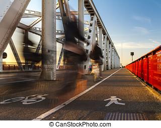 Crossing the bridge by bike in the evening sun between...