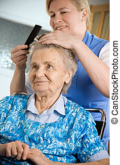 nursing home - Nurse dressing the hair of a senior woman