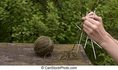 Knitting in the garden - Woman knitting outdoors in the...