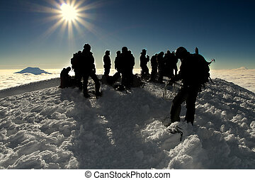 group of people on the summit of a high mountain - a number...