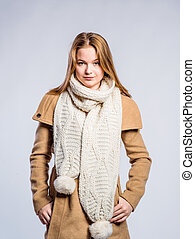 Girl in brown coat and knitted scarf, studio shot - Teenage...