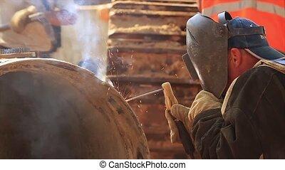 Welder working on a pipeline. Close up shot welder until...