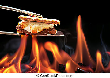 Smore Cooking Over Campfire - Smore cooking over fire with...