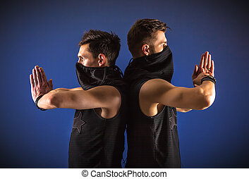 Two male dancers posing in ninja costumes against blue background.