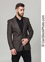 Studio portrait of handsome elegant young man in brown...