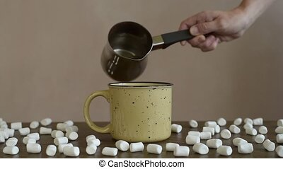 Pouring coffee into a mug - Female hand pouring coffee into...