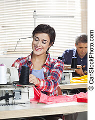 Happy Female Tailor Working In Sewing Factory - Happy female...