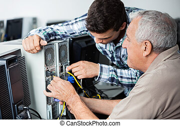 Teacher And Senior Man Fixing Computer In Class - Male...