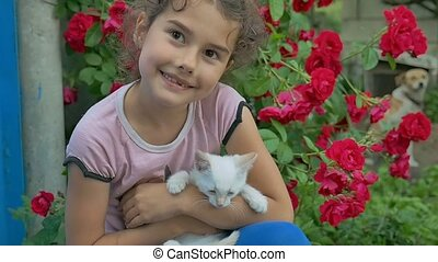 brunette teen girl holding kitten in her cat arms love...