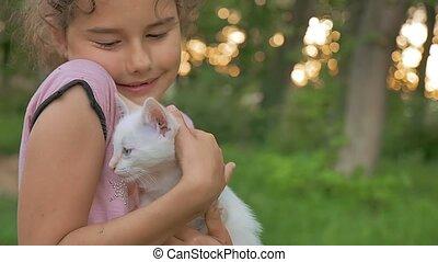 girl brunette holding kitten in her cat arms love outdoors -...