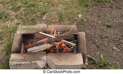 Putting firewood into the fire in the summer garden.