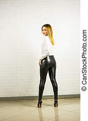Woman wearing black leather pants and high heel shoes.