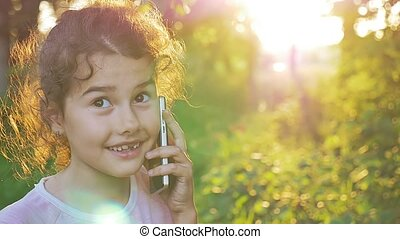 girl teen talking on the phone behind sunset golden hour...